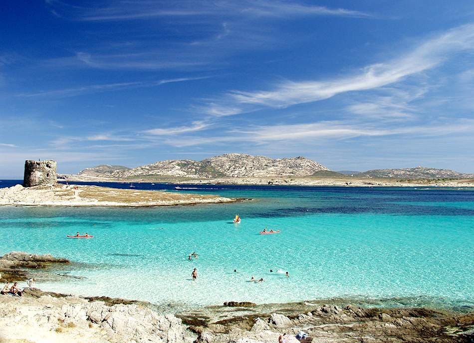 Sardinia - La Pelosa beach, one of the most beautiful destinations in Sardinia where fine sand as tiny as flour and shallow sea that shifts from aquamarine to topaz both blend with the sky, creating a captivating and breathtaking landscape.